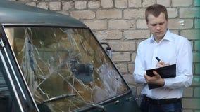 O homem inspeciona um minibus quebrado do carro, seguro video estoque