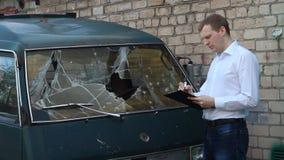 O homem inspeciona um minibus quebrado do carro, seguro vídeos de arquivo
