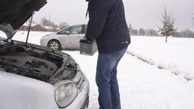O homem instala a bateria no carro no inverno, o começo do problema o carro no mo frio, lento video estoque