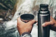 O homem irreconhecível do caminhante derrama o chá ou o café da garrafa térmica que caminha o conceito das férias do curso imagens de stock royalty free
