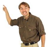 O homem irritado aponta por sua mão na placa atrás dele Fotografia de Stock Royalty Free