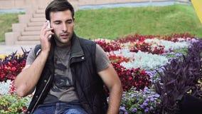 O homem italiano moreno 'sexy' esperto bonito que senta-se no parque olha para a frente a encontrar a fala no telefone, bom tempo filme