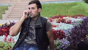 O homem italiano moreno 'sexy' esperto bonito que senta-se no parque olha para a frente a encontrar a fala no telefone, bom tempo vídeos de arquivo