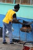 O homem jamaicano está cozinhando a galinha do empurrão foto de stock