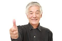 O homem japonês superior com polegares levanta o gesto Fotos de Stock