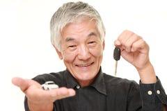 O homem japonês superior pega um carro novo Foto de Stock Royalty Free