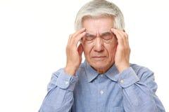 O homem japonês superior sofre da dor de cabeça Fotos de Stock