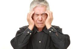 O homem japonês superior sofre da dor de cabeça Fotos de Stock Royalty Free