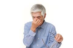O homem japonês superior sofre do Asthenopia Fotos de Stock Royalty Free
