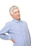o homem japonês superior sofre do lumbago Imagem de Stock Royalty Free