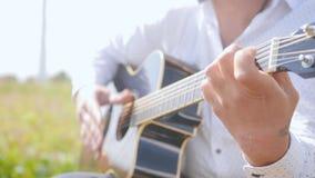 O homem joga a guitarra e canta-a na natureza Cordas tocantes da guitarra do guitarrista Feche acima do tiro vídeos de arquivo