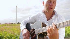 O homem joga a guitarra e canta-a no campo na natureza Cordas tocantes da guitarra do guitarrista Tiro m?dio filme
