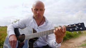 O homem joga a guitarra e canta-a no campo na natureza Cordas tocantes da guitarra do guitarrista Tiro m?dio vídeos de arquivo