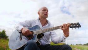 O homem joga a guitarra e canta-a no campo na natureza Cordas tocantes da guitarra do guitarrista Tiro m?dio video estoque