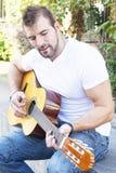 O homem joga a guitarra no parque. foto de stock