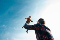 O homem joga o menino no céu Foto de Stock Royalty Free