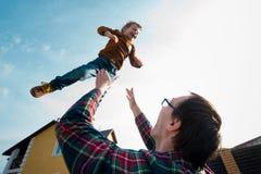 O homem joga o menino no céu Fotografia de Stock Royalty Free
