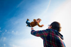 O homem joga o menino no céu Imagem de Stock Royalty Free