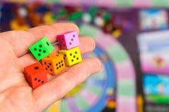 O homem joga os dados no campo de ação Jogos de mesa do jogo dos povos Fotografia de Stock Royalty Free