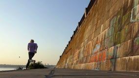 O homem joga uma bola em uma parede do banco de rio mas não trava no slo-mo vídeos de arquivo