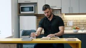 O homem lê um livro que senta-se na cozinha em casa e na água das bebidas video estoque