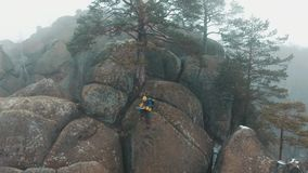 O homem lê um mapa que senta-se na parte superior da montanha coberta com a névoa video estoque