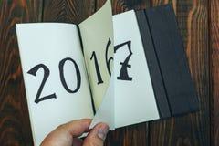 O homem lança a folha do bloco de notas em uma tabela de madeira 2016 estão girando, 2017 estão abrindo alto Foto de Stock