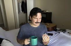 O homem latino-americano olha o comprimido antes de tomá-lo com uma bebida Fotos de Stock