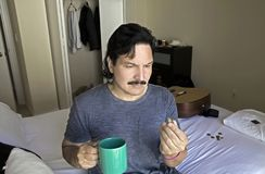 O homem latino-americano olha o comprimido do óleo de peixes antes de tomá-lo com bevera Foto de Stock