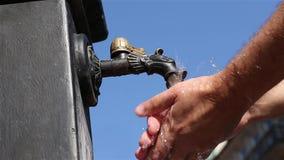 O homem lava suas mãos com água fria de uma torneira velha do ferro na rua da cidade velha filme