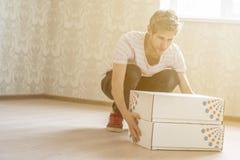 O homem leva caixas e movimento dos desenhos animados ao conceito liso f da casa nova imagens de stock royalty free