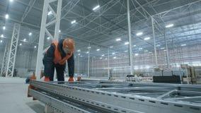 O homem leva a construção do metal no armazém moderno novo da indústria filme