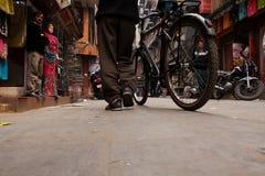 O homem leva sua bicicleta ao longo da rua de Kathmandu fotografia de stock