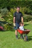 O homem leva sua filha em um carrinho de mão Fotos de Stock Royalty Free