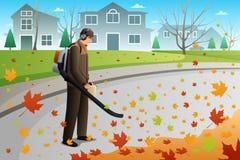 O homem limpa as folhas durante o outono usando um ventilador Imagem de Stock Royalty Free