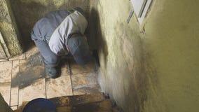 O homem limpa as paredes da sujeira forte com uma escova e um pano O trabalhador lava as paredes do corredor manualmente Molde e filme
