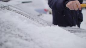 O homem limpa o carro da neve com uma escova video estoque