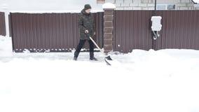 O homem limpa a estrada coberto de neve com uma pá filme