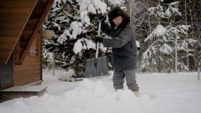O homem limpa a jarda com uma pá das pilhas da neve no inverno vídeos de arquivo
