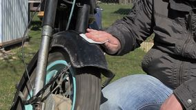 O homem limpa a motocicleta velha video estoque