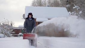O homem limpa a neve com o fundo do arado de neve da casa de madeira no inverno filme