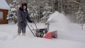 O homem limpa a neve com o fundo do arado de neve da casa de madeira no inverno video estoque