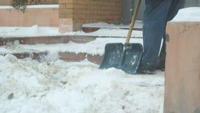 O homem limpa a neve com a pá filme