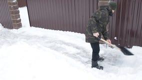 O homem limpa a neve com uma pá grande perto da casa video estoque
