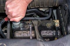 O homem limpa os terminais de uma bateria em um caminhão imagem de stock royalty free