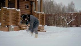 O homem limpa a pá na jarda do inverno da neve no fundo de uma casa de madeira video estoque