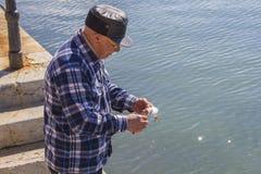 O homem limpa peixes no cais Imagens de Stock Royalty Free