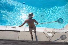 O homem limpa a piscina imagem de stock
