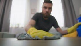 O homem limpa a poeira na mesa de centro vídeos de arquivo