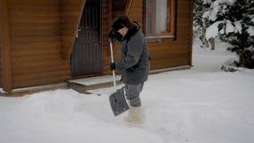 O homem limpa uma jarda da pá da neve no fundo de uma casa de madeira no inverno vídeos de arquivo
